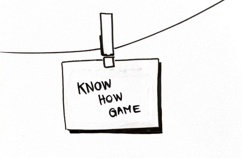 Skizzierter Notizzettel mit der Aufschrift Know-How Game mit einer Klammer an einer Leine aufgehängt